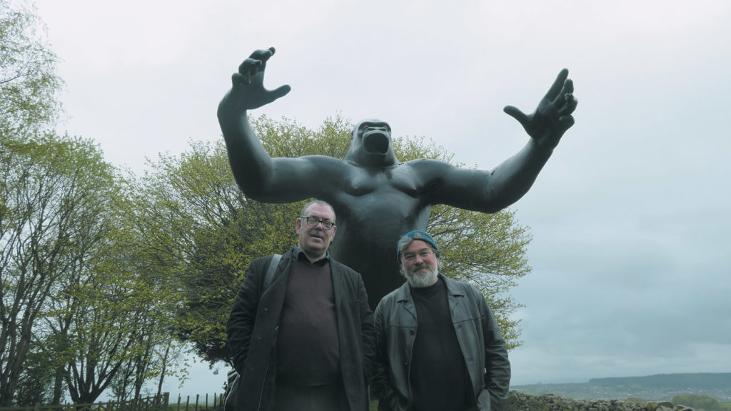 The musician Robert Lloyd and the comedian Stewart Lee in front of Nicholas Monro's sculpture of King Kong, Cumbria, England; from King Rocker
